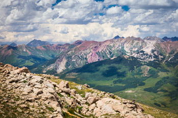 High in the Rocky Mountains of Colorado, displaying bright red stone, the San Juan Mountains stand tall under a summer sky filled with bright white, puffy clouds. Prints available; please contact us for details.