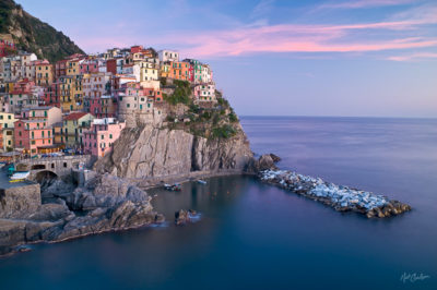 Pink clouds form a delicate backdrop for the pastel, picturesque village of Manarola, on the Ligurian coast of northwest Italy. Manarola is one of the Cinque Terre, or Five Lands; old towns that form a national park in this uniqe part of Italy. The breakwater is made of large marble blocks from nearby quarries.