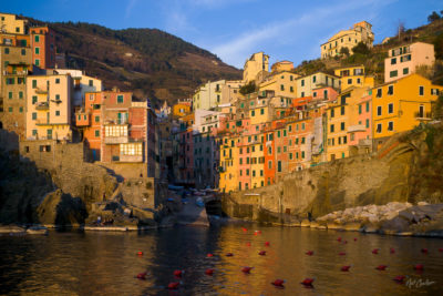 Riomaggiore, Italy - the warming rays of the setting sun illuminate the colorful buildings stacked on the cliffsides of a small harbor in the Mediterranean.