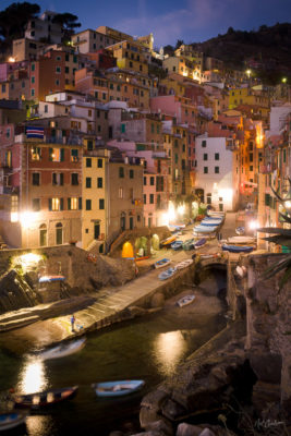 """Riomaggiore, Italy - Lights reflect in the small harbor of this seaside fishing village shortly after sunset. Riomaggiore is part of the Cinque Terre, or """"Five Lands"""", a string of popular resort villages on the northwestern coast of Italy."""