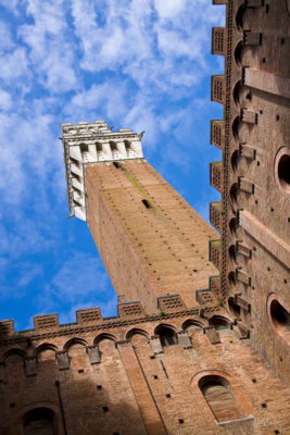 Siena, Toscana, Italia - as seen looking upward from a small courtyard, the main bell tower of the medieval town of Siena rises into a blue sky dotted with white clouds.