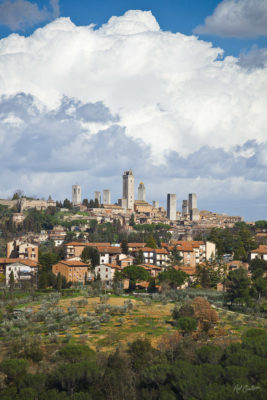 San Gimignano, Tuscany, Italy - the famous towers of the medieval town rise high above the surrounding village. Behind, huge, billowing cumulus clouds rise into the sky.