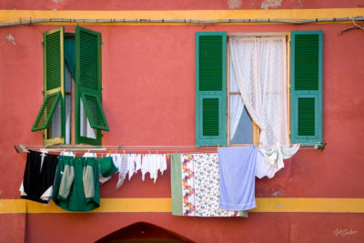 Vernazza, Italy - clothes dry on a line outside the green shutters of the windows of a building in the Ligurian of Vernazza.